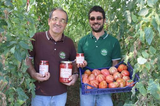 """Franco e Lele Bressi in una serra dell'azienda con le confezioni di """"Tumatì"""" e una cassetta di pomodori appena raccolti"""