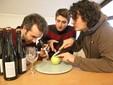 """I tre giovani testano una mela con il rifrattometro accanto alle bottiglie di """"Arvirà"""" pronte per la vendita"""