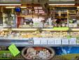 """La struttura di vendita dei formaggi di Michele e Pierangela con i cartelli """"Su questo banco si parla anche piemontese"""""""