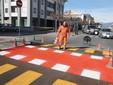 Un addetto alla tracciatura delle strisce pedonali al lavoro sull'attraversamento rialzato tra corso Gramsci e via Bongioanni