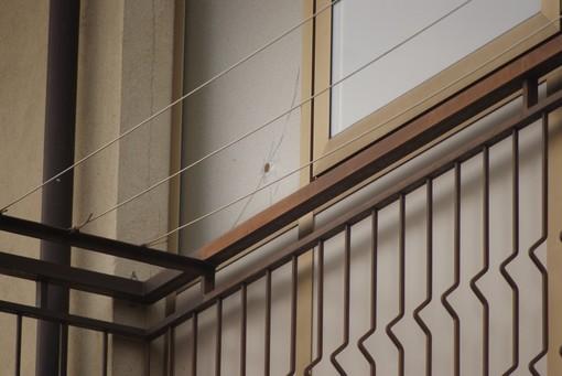 Nel fotoservizio di Francesco Ameglio (© Francesco Ameglio) il luogo del delitto il giorno dopo: la pallottola che ha trapassato la finestra di un appartamento vicino, i carabinieri mentre effettuano i rilievi