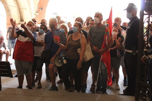 I lavoratori che hanno assistito alla seduta dal maxischermo allestito sotto i portici del municipio