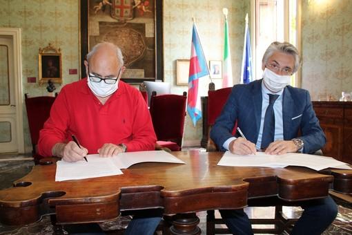 La firma dell'intesa tra il sindaco albese Carlo Bo, a destra, e il collega govonese Elio Sorba