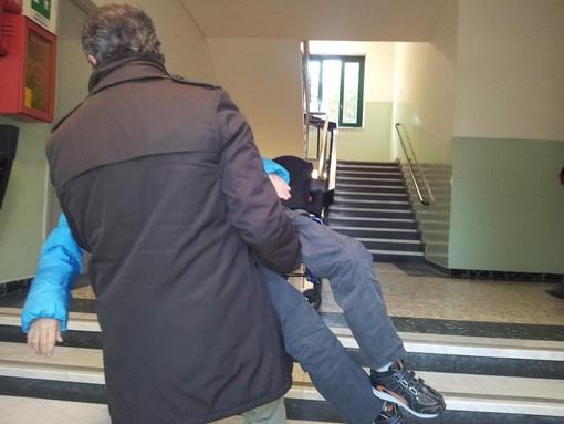 Fabio Di Stefano mentre solleva il figlio in braccio per portarlo a scuola