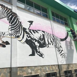 """Lo street artist Iena Cruz dipinge la facciata della scuola media di Madonna dell'Olmo: """"Sarà la più bella e la più green della città"""" [VIDEO]"""