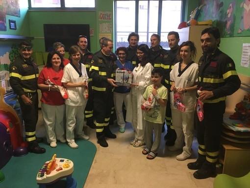 Oscar Pozzetti, al centro, la scorsa Epifania, mentre consegna l'aerosol donato dai vigili del Fuoco di Alba alla dottoressa Rosana Fernandez responsabile del reparto di Pediatria