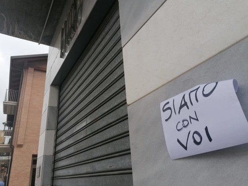 Un cartello di solidarietà appeso di fianco all'ingresso della gioielleria Roggero all'indomani della tragedia